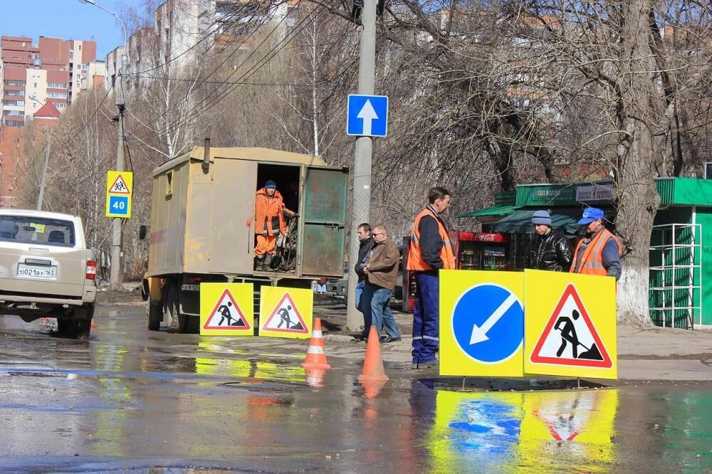 """Знаки """"Дорожные работы"""" с указанием места объезда на фоне рабочих"""