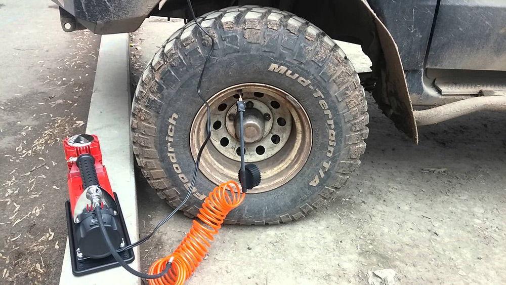 Автомобильный компрессор качает колесо