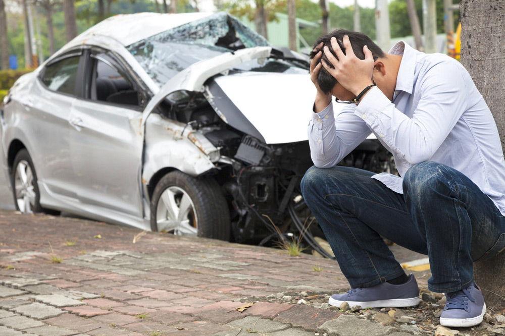 Парень сидит рядом с разбитой машиной