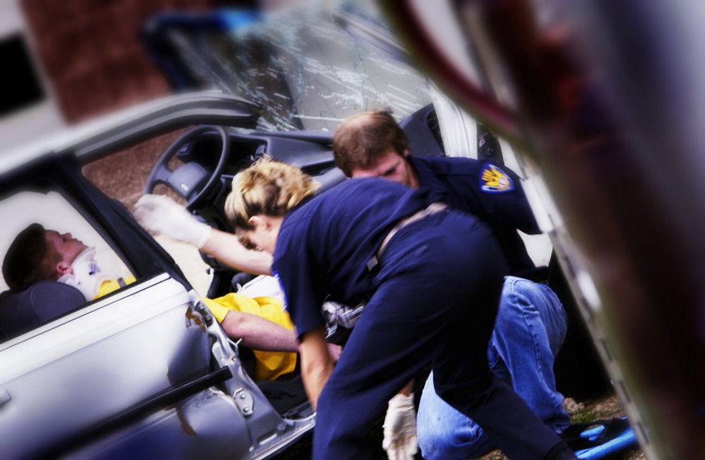 Двое человек достают пострадавшего с машины