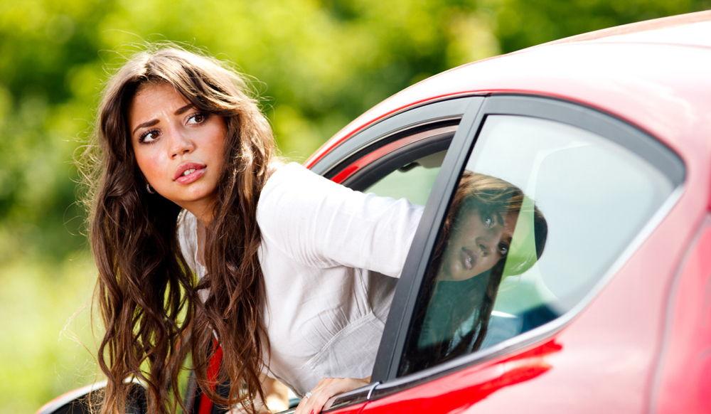 Девушка сдает назад на красной машине