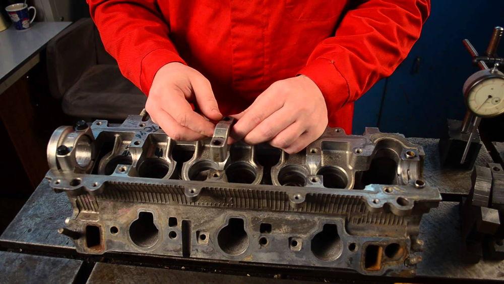 Человек ремонтирует двигатель
