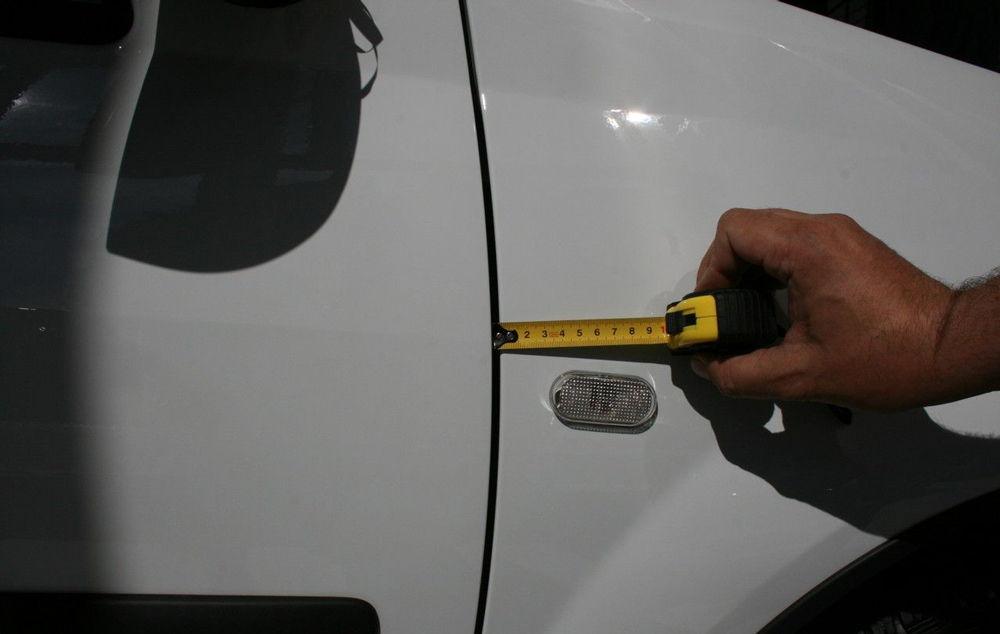Человек меряет рулеткой зазор авто