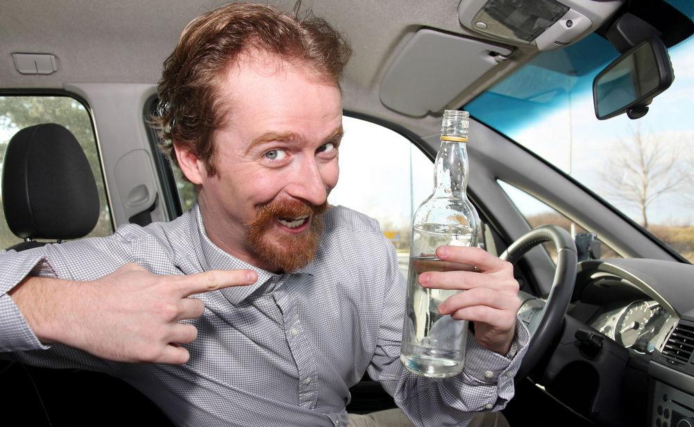 Человек выпивает за рулем